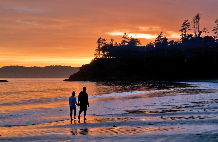 Couple walking on the beach at sunset in Tofino, B.C.