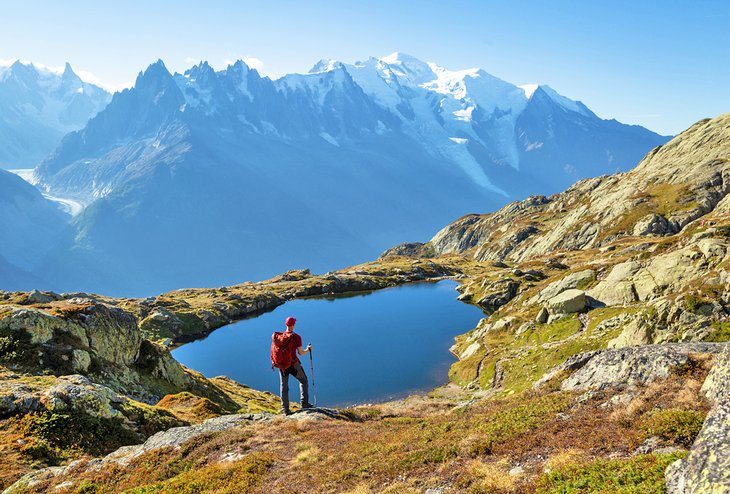 Hiker gazing over Lac de Cheserys on the famous Tour du Mont Blanc
