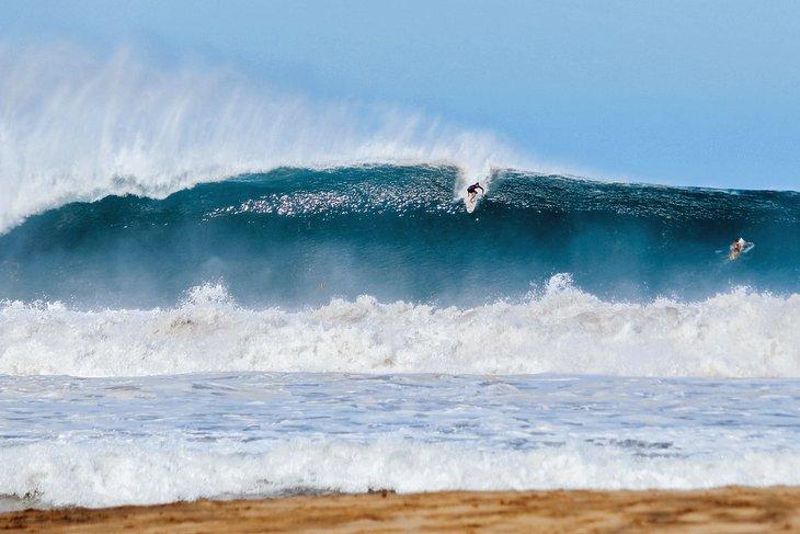 Surfista despegando en una gran ola de Puerto Escondido