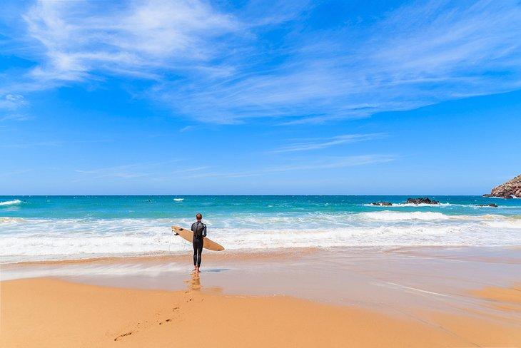 Surfista comprobando las olas en Praia do Amado